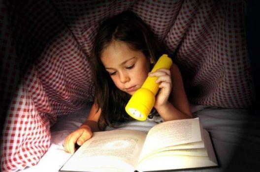 девочка читает книгу под одеялом с фонариком