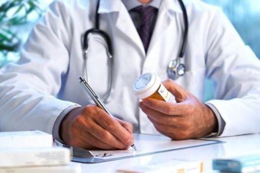 врач выписывает рецепт на лекарства