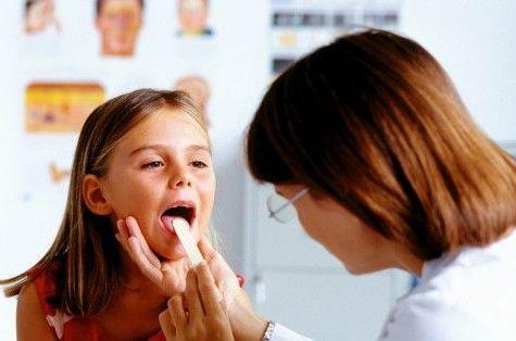 врач смотрит горло у девочки